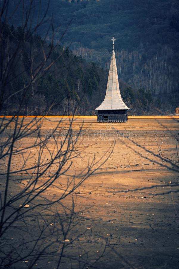 The tower of a church located in a village flooded with sterile waste from a mining company in a dramatic and desolate place stock images