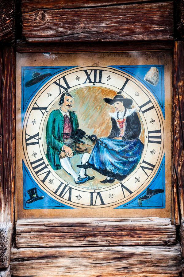 Tower clock in wooden frame with history painting. Analog clock with roman numerals. Vintage retro wooden frame. Painting depicting a man and a woman in vintage royalty free stock image