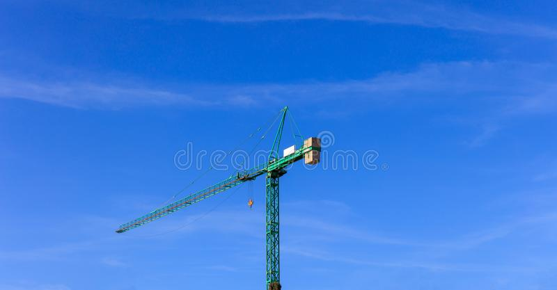 Tower crane ready for lifting on blue sky background. Space for text. Tower construction crane ready for lifting. Blue sky backdrop. Space for text stock images
