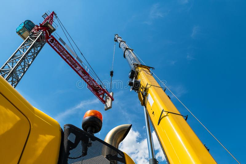 Tower crane assembly. Lifting device installation. Construction site. Placing a concrete counterweight by high telescopic boom of yellow mobile hoist machine royalty free stock image