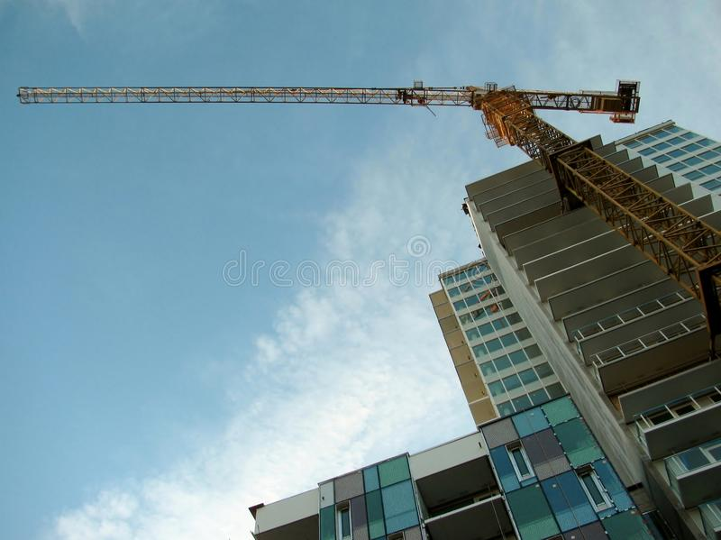 Tower crane attached to concrete building during construction. stock images