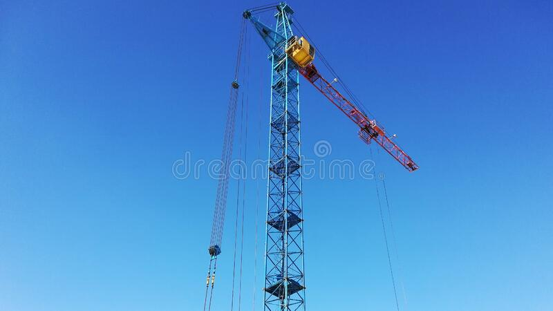 Tower crane on a background of blue sky stock photos