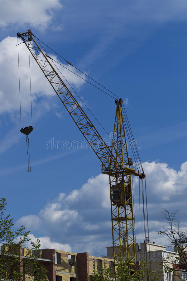 Tower crane on the background of the building is building. Lifting tower crane on a background of building under construction and blue sky with clouds, sunshine royalty free stock images