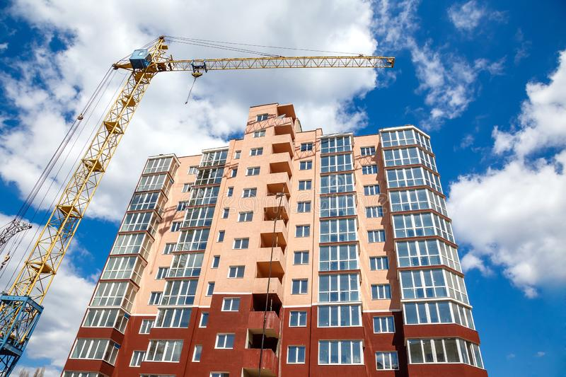 Tower crane building modern apartment house on a background of blue cloudy sky at sunny day. Real estate concept. Tower crane  building new modern  apartment royalty free stock photos