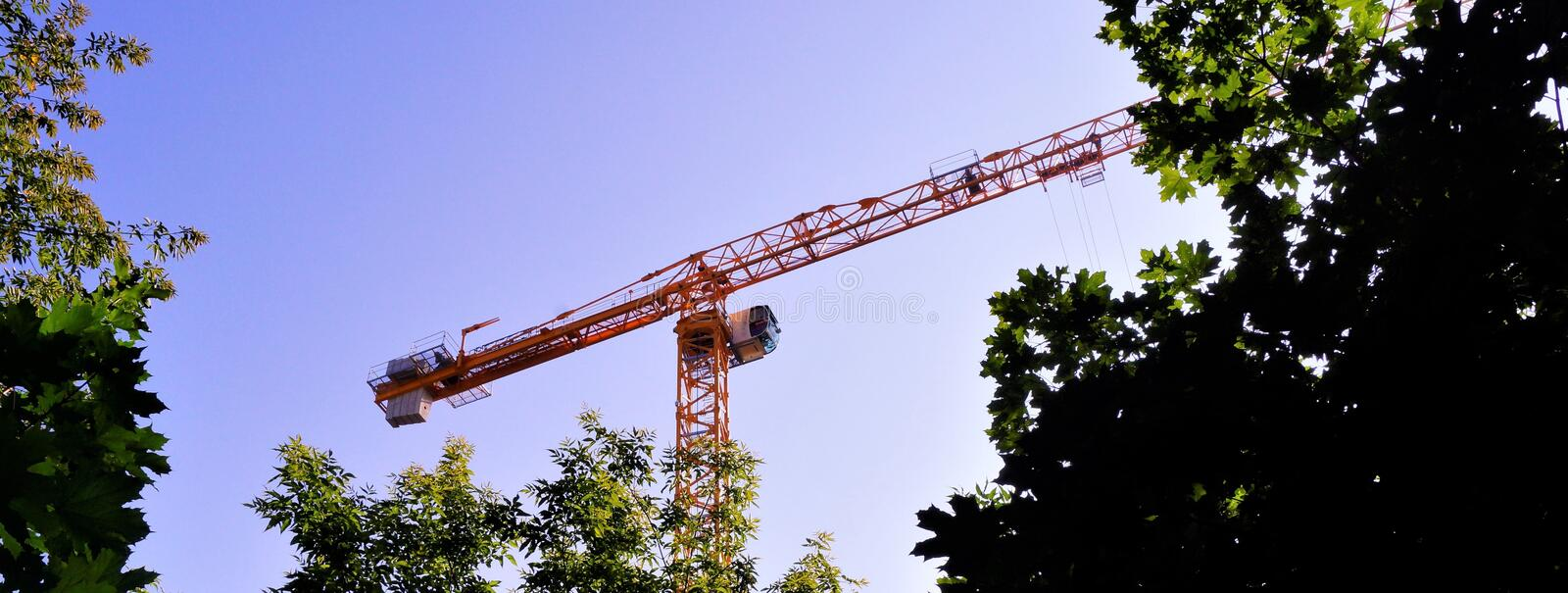 Tower crane construction rotary with an arrow on the background of the sky and trees. Lifting machine spatial movement of goods,. With the engagement of hook stock photos