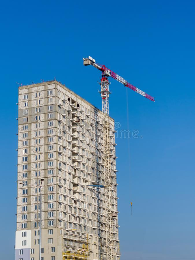 Tower crane and high-rise apartment building under construction against blue sky. A clear sunny day. Theme of construction royalty free stock images