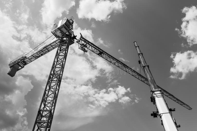 Tower crane installation. Black and white silhouette. Work at heights. Artistic construction background with sky and clouds. Telescopic boom of lifting device royalty free stock photos