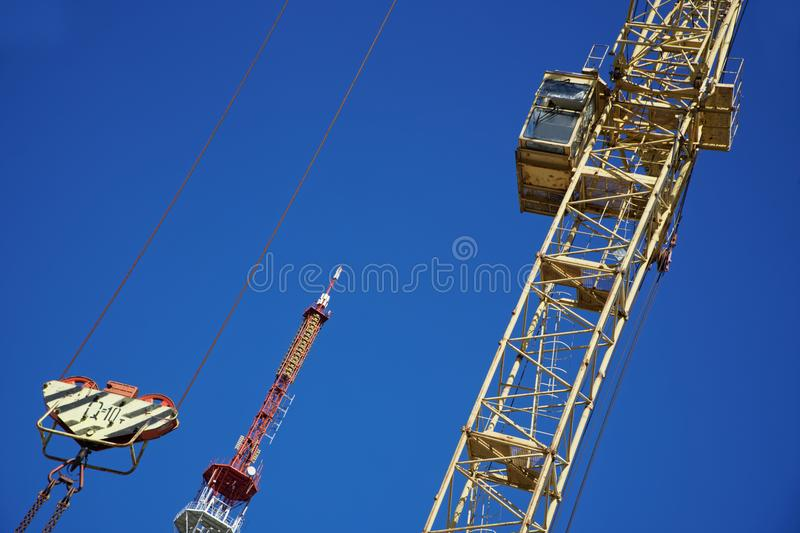 Tower crane with a lifting capacity of 10 tons. Tower crane with a lifting capacity of 10 tons against a blue sky and a TV tower. Construction machinery and royalty free stock images
