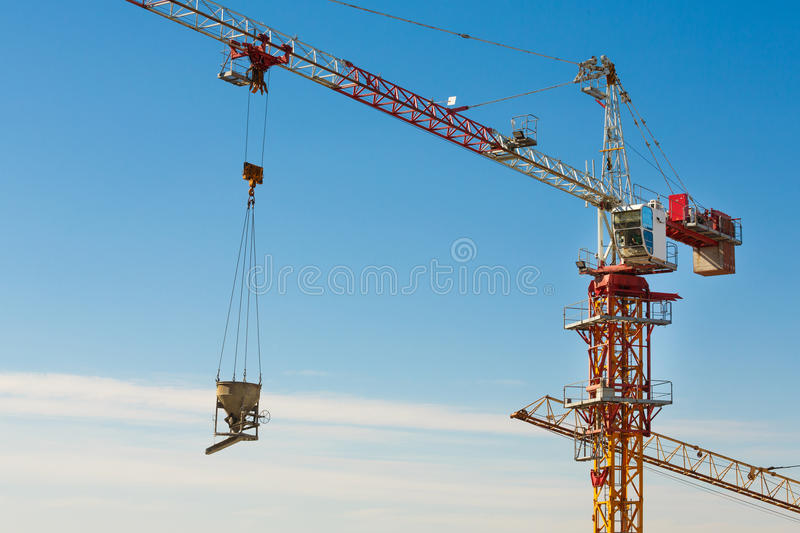 Download Tower Crane Lifting Up A Cement Bucket At Construction Area Stock Image