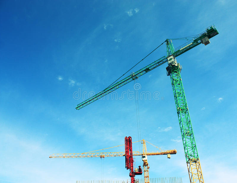 Tower crane. Several cranes bright coloring on a background of blue sky