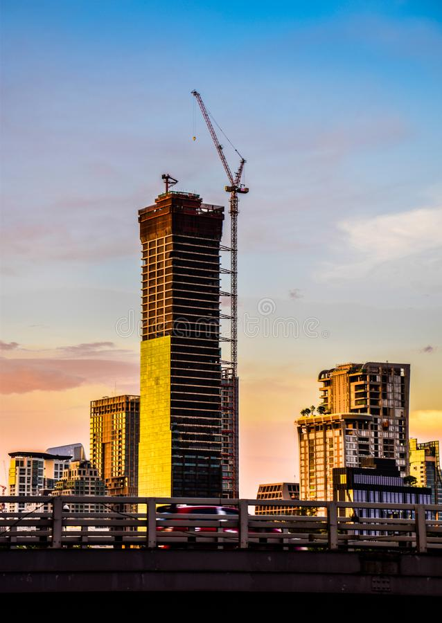 Tower crane on top of an unfinished building in the evening at Bangkok, Thailand stock photos