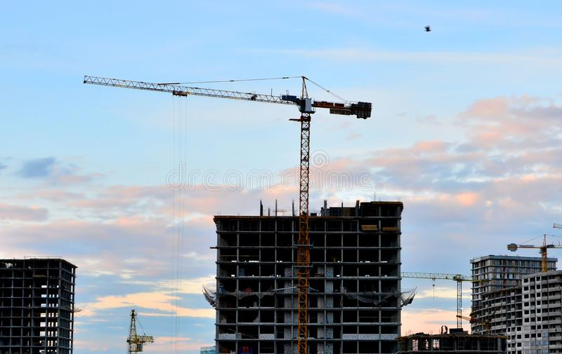Tower cranes at construction site in the sunset sky. Image royalty free stock photo