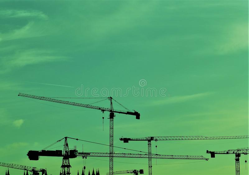 Tower cranes against turquoise evening sky royalty free stock photo