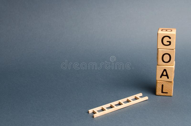 A tower of cubes with an inscription goal and a fallen ladder. Tool for success. Don`t give up half way. The concept of achieving stock images
