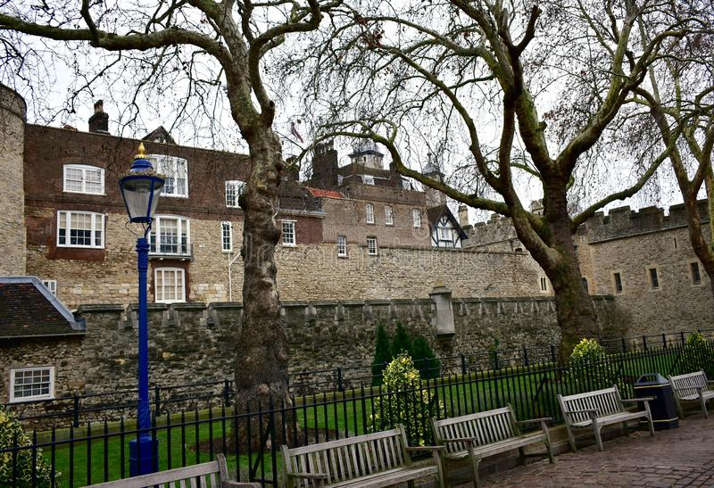 The Tower of London with a blue and golden streetlight, trees and wooden benches. London, United Kingdom. stock photo