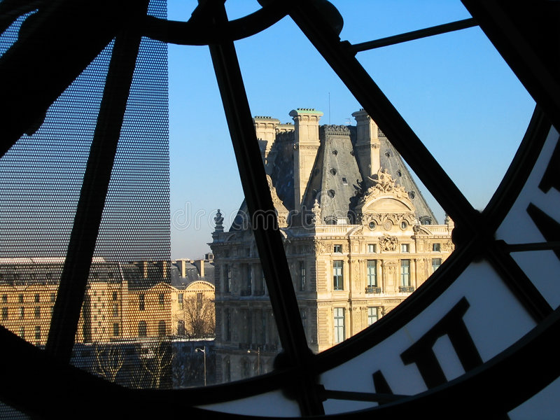 Tower of Louvre through Orsay clock. Tower of Louvre palace through the Orsay museum clock in Paris, France stock image