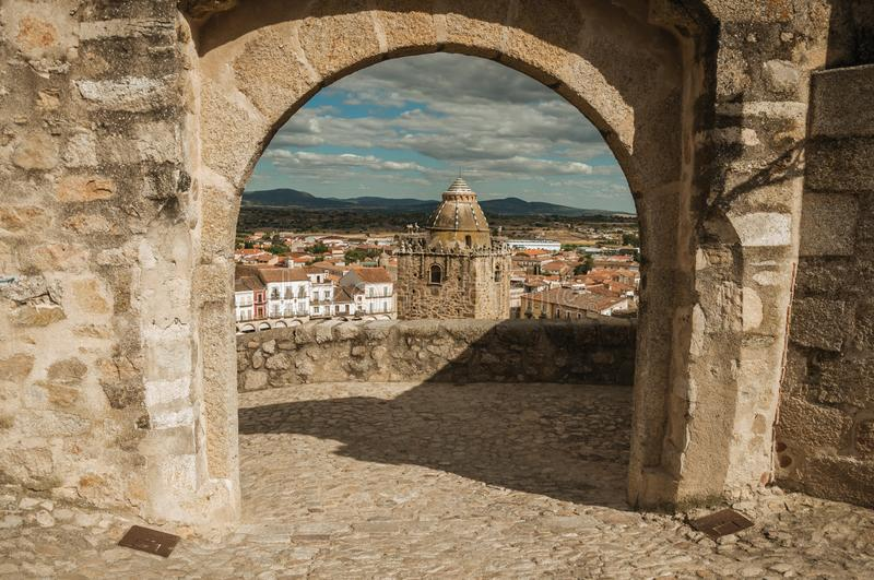 Tower with old buildings seen through arched stone gateway at Trujillo royalty free stock photo
