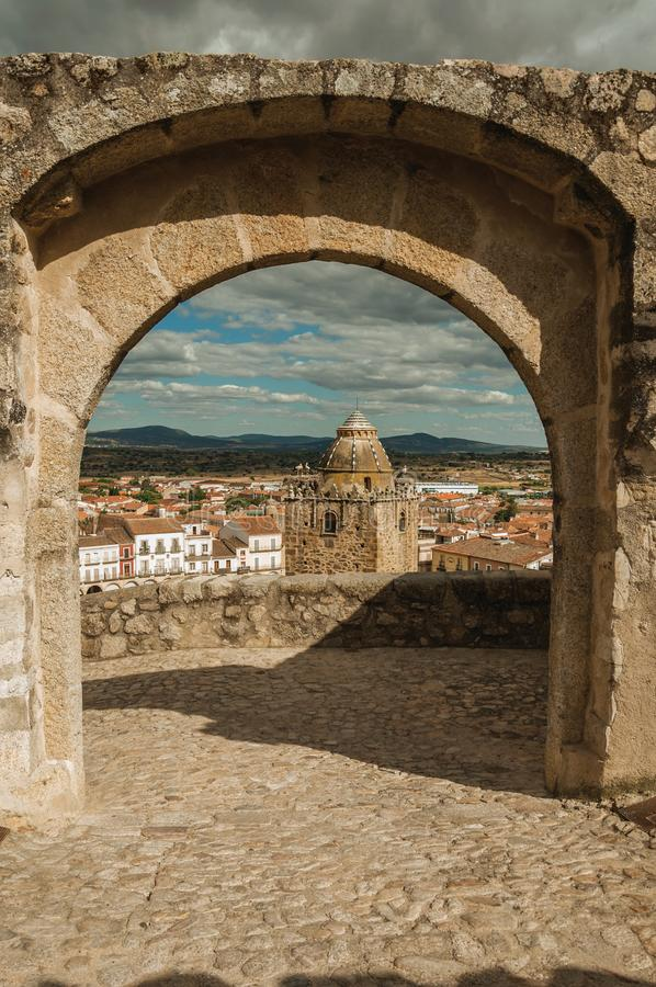 Tower with old buildings seen through arched stone gateway at Trujillo royalty free stock photography