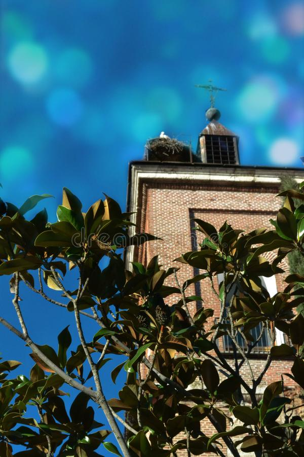 Tower of the old church with a cross and a stork nest royalty free stock photography