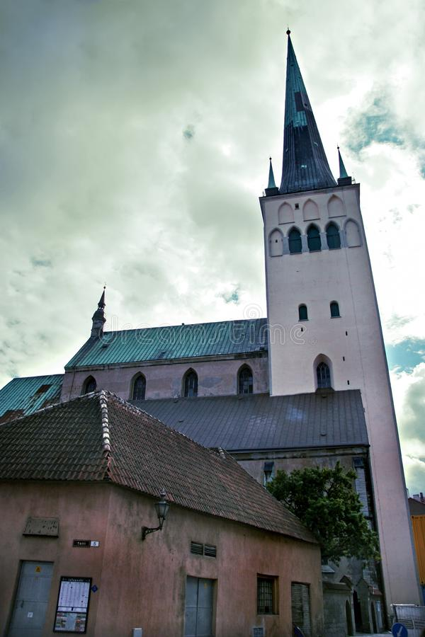 Tower Oleviste with old extensions in the old city of Tallinn with clouds in the sky. royalty free stock photography