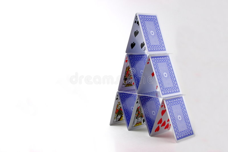 Tower of playing cards. Tower of balancing playing cards on white background with copy space stock image
