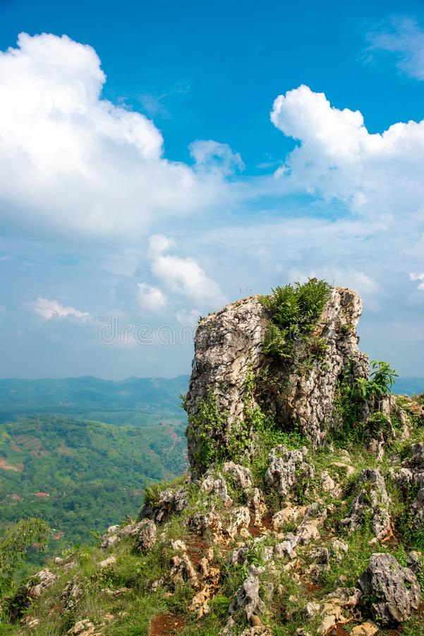 Tower of Rock or Stone with White Cloud and Blue Sky and Blur Scenic Landscape Valley Below. For Background or backdrop stock image