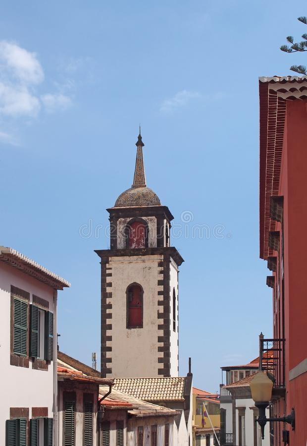 The tower of São Pedro church in funchal a historic 17th century building in madeira notable for the colored tiles on the spire. Surrounds by the roofs of stock photos