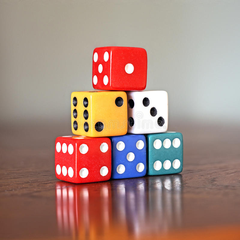 Tower of six colored dice with numbers from 1 to 6 on a wooden royalty free stock image