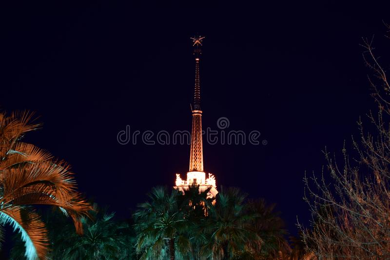 Tower with a spire illuminated by spotlights at night. Sight of the city of Sochi. Beautiful spire of the building of the marine station. At night, fully stock image