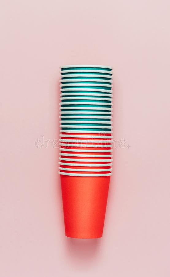 Tower stack of paper cups on pink background royalty free stock photography