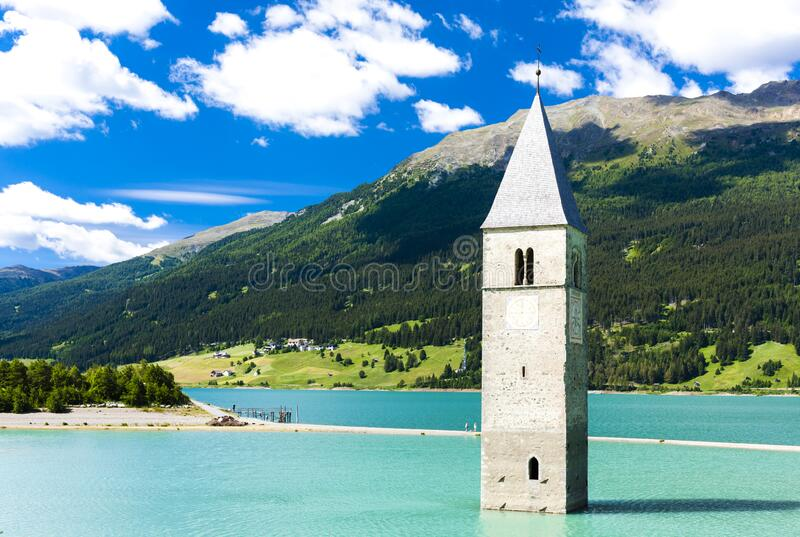 Tower of sunken church in Resia lake, South Tyrol, Italy stock photography