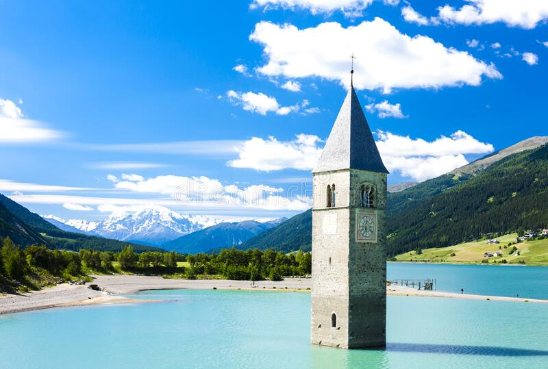Tower of sunken church in Resia lake, South Tyrol, Italy royalty free stock photo