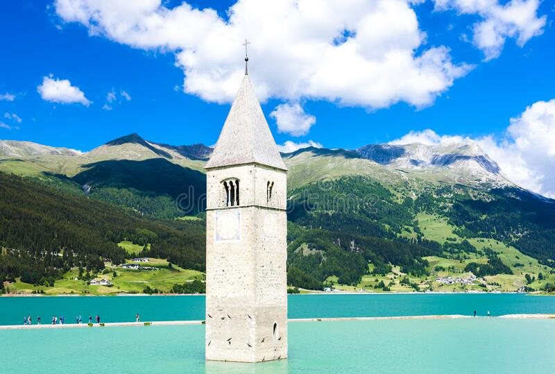 Tower of sunken church in Resia lake, South Tyrol, Italy royalty free stock image