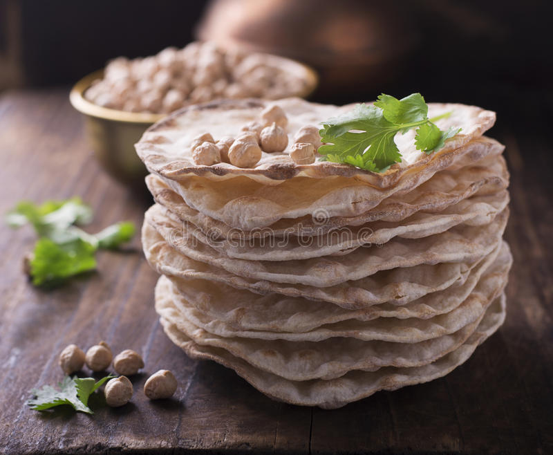 Tower thin crispy loaves of useful home cakes with chick-pea flour for vegetarinskogo and healthy eating. On a dark. Tower thin crispy loaves of useful home royalty free stock photo