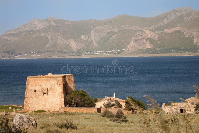 Tower of the Tonnara of Monte Cofano, Sicily. The fortified tower next to the Tonnara of Monte Cofano near San Vito lo Capo in the Gulf of Macari in northern royalty free stock photo