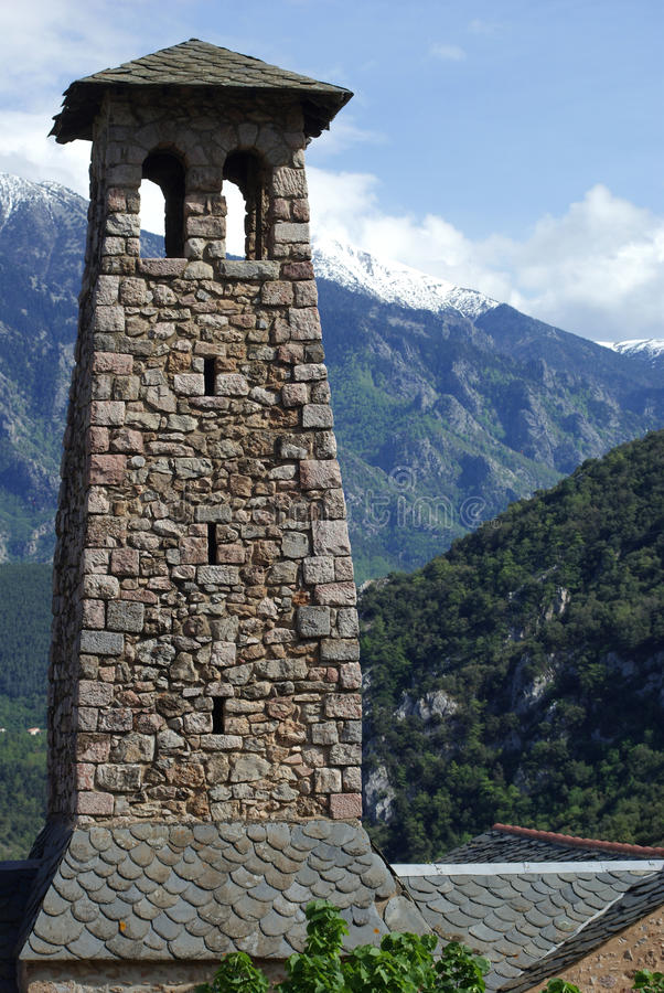 Tower at Villefrance-de-Conflent. Tower with windows at villefranche-de-Conflent and a blue sky and snowy mountains in the background stock image