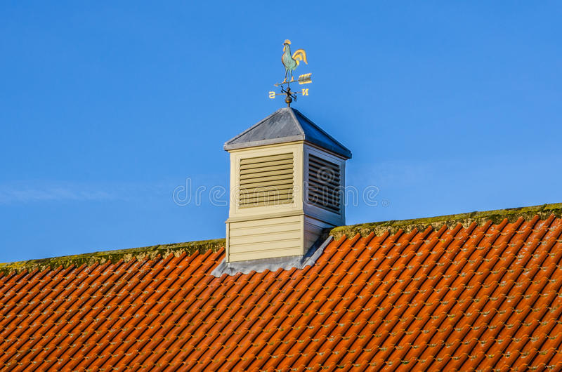 Tower and Weather Vane on Red Tiled Roof. With Blue Sky royalty free stock photography