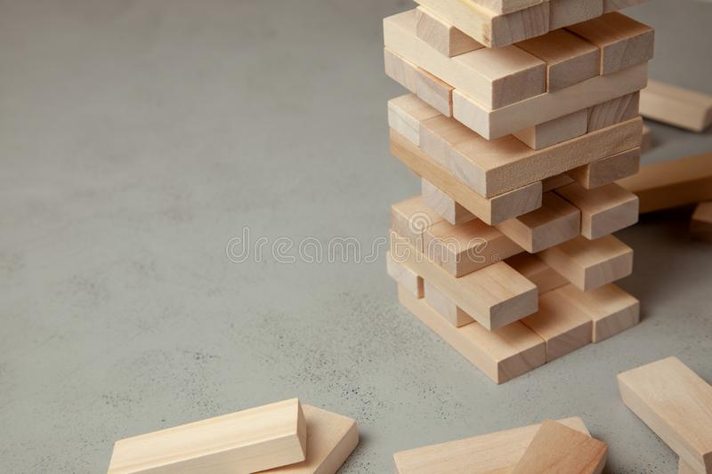 Tower of wooden blocks on gray background. Board game for the whole family or party. Concept of building business or building team stock images