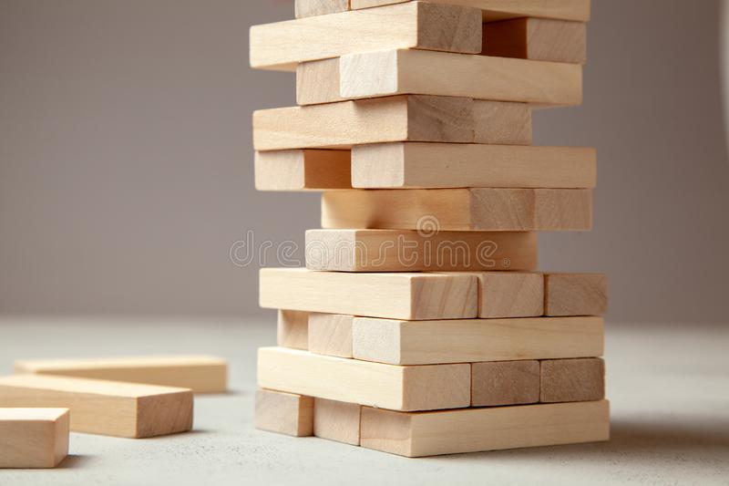 Tower of wooden blocks on gray background. Board game for the whole family or party. Concept of building business or building team royalty free stock photography