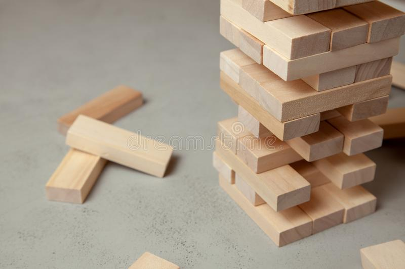 Tower of wooden blocks on gray background. Board game for the whole family or party. Concept of building business or building team stock photo