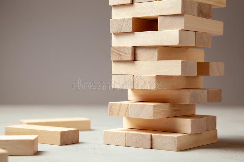 Tower of wooden blocks on gray background. Board game for the whole family or party. Concept of building business royalty free stock photo
