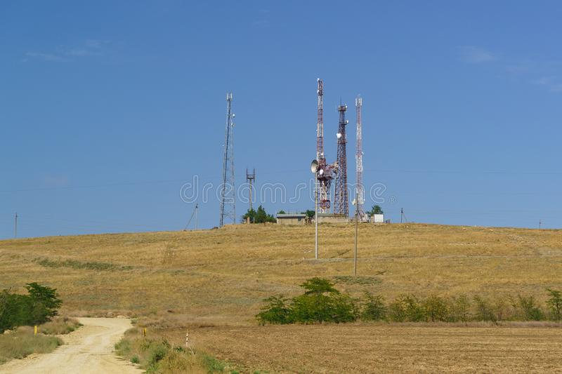 Towers with antennas and transmitters on a small hill. Sunny day stock photo