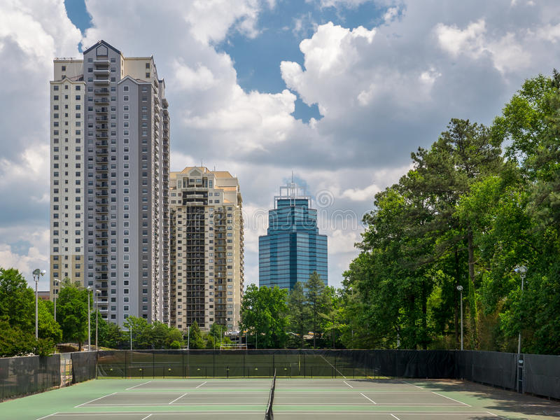 Towers Behind a Park. Residential and buisness towers standing tall behind tennis courts in a park in Sandy Springs, Georgia royalty free stock photos
