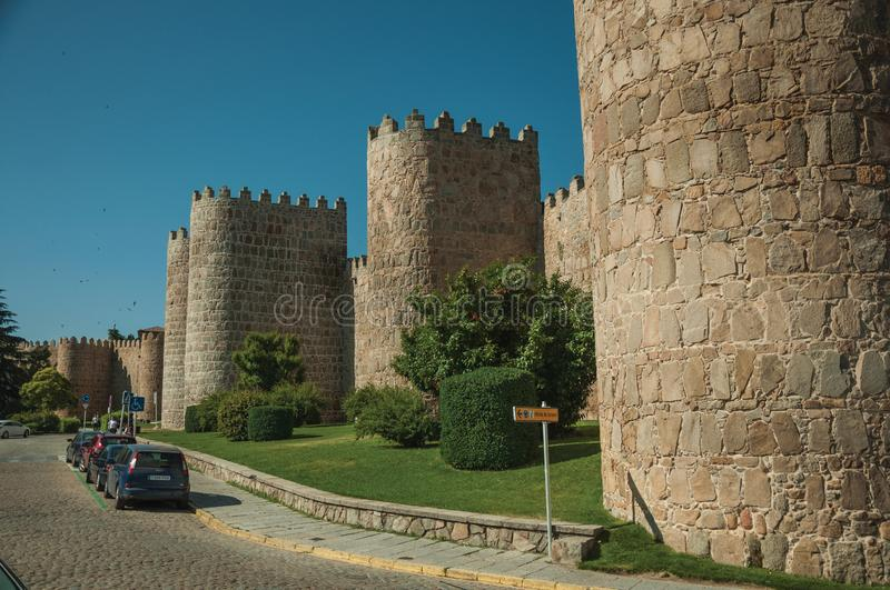 Towers on city wall next to a street at Avila. Avila, Spain - July 22, 2018. Towers on city wall made of stone in Romanesque style next to a street at Avila. It royalty free stock photos
