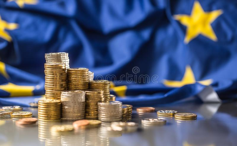 Towers with euro coins and flag of European Union in the background. Money cash currency bank finance business symbol financial economy yellow stars blue royalty free stock photo