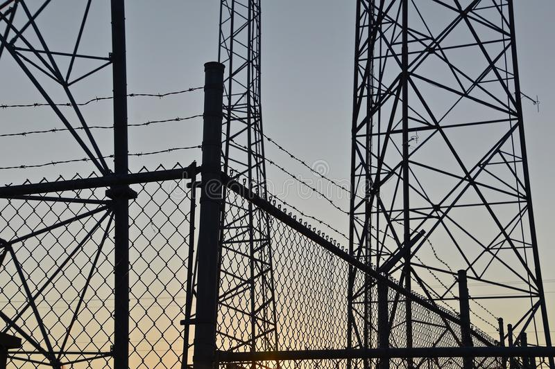 Towers and fences silhouetted in the morning sunrise. Telecommunication and radio relay antenna radio towers are silhouetted in the morning sky royalty free stock photography