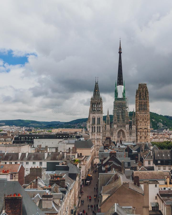 Towers and front façade of the Rouen Cathedral over medieval street and buildings of the city center of Rouen, France stock photos
