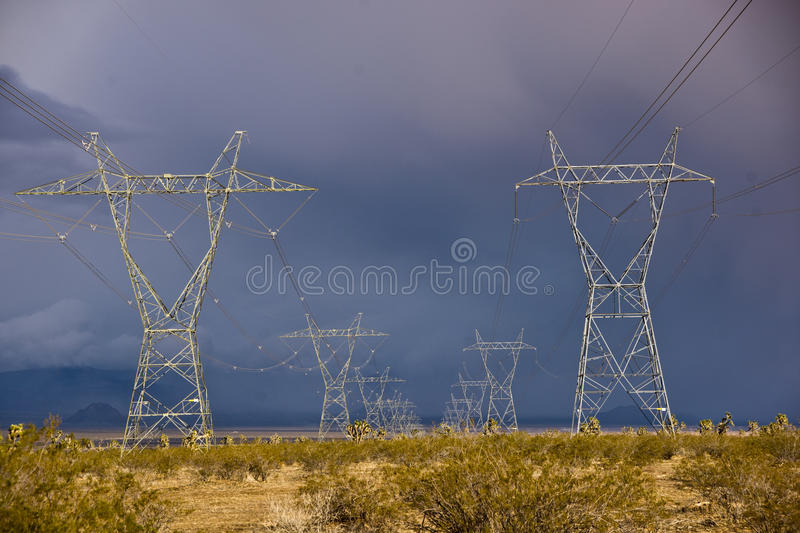 Towers of Power. Huge electrical towers carry power across the US Southwest desert on a stromy day royalty free stock image