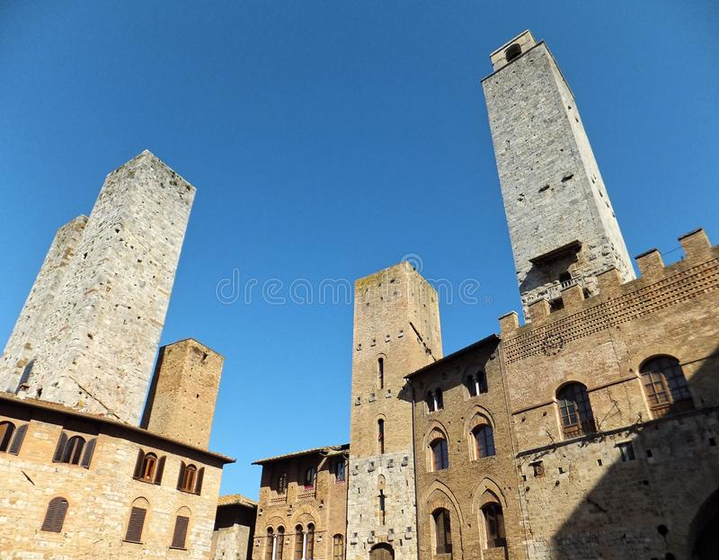 Towers of San Gimignano in Tuscany against deep blue sky, surrounding a square lined with old historical buildings stock photography