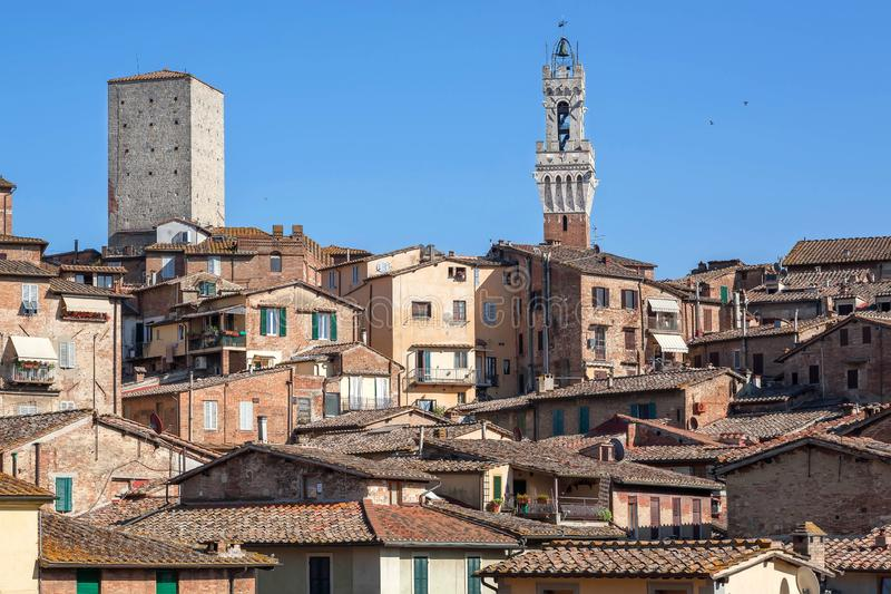 Towers and stone houses of Siena, Tuscany. Tile roofs and brick structures in Italy. UNESCO World Heritage Site.  royalty free stock image